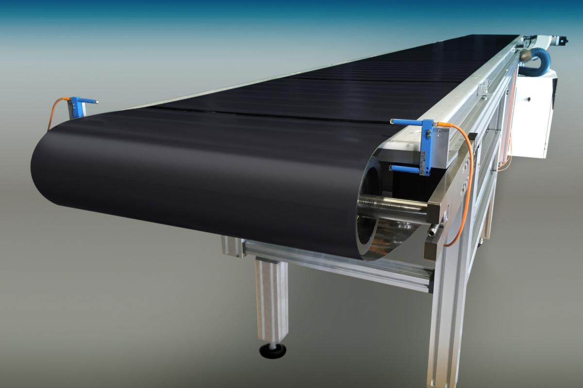 Système convoyeur avec tapis métallique perforé pour le transport sous vide de produits.